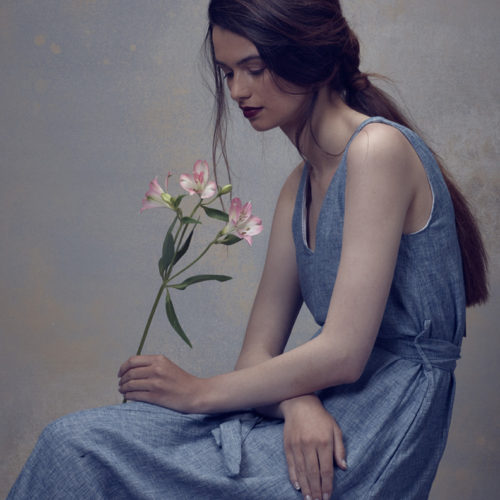 Makeup for fashion shoot - model in blue dress holding a flower