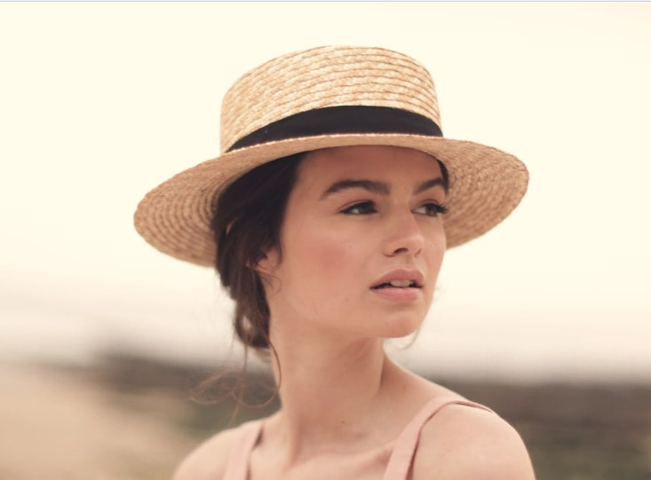Makeup for fashion shoot video - model wearing straw hat looking out to sea