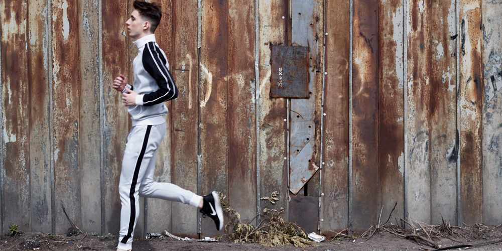 Male styling - model jogging past rusty fence